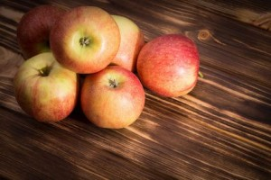 red apples on the brown wooden background.